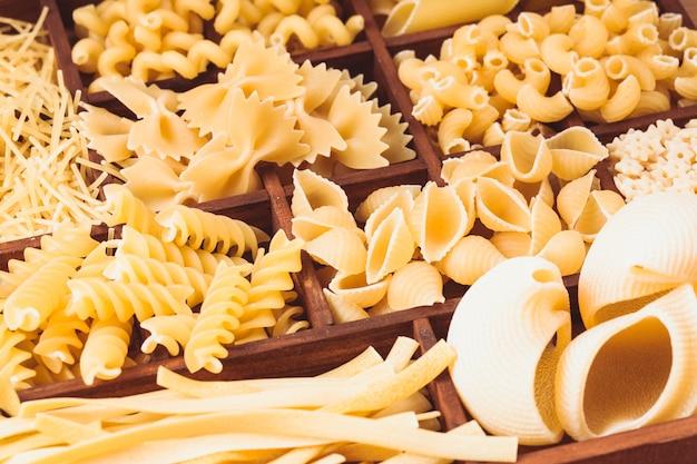 Différents types de pâtes dans la boîte en bois sur la table