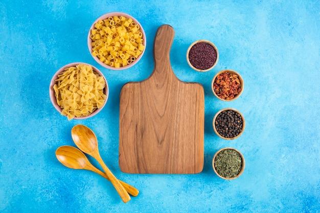 Différents types de pâtes dans un bol et une planche à découper en bois sur une surface bleue.
