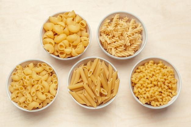 Différents types de pâtes dans des bols sur la table.