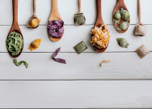 Différents types de pâtes dans des cuillères en bois sur la table. vue de dessus