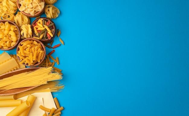 Différents types de pâtes sur un espace bleu avec espace de copie pour le texte