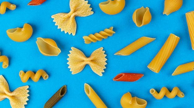 Différents types de pâtes sur fond bleu, vue de dessus, composition à plat