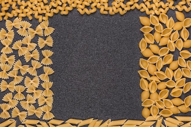 Différents types de pâtes sur fond gris. cadre en macaroni.