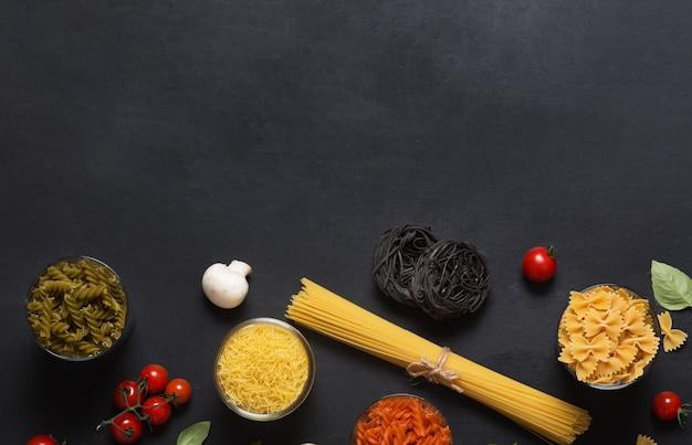 Différents types de pâtes italiennes aux légumes sur le tableau noir