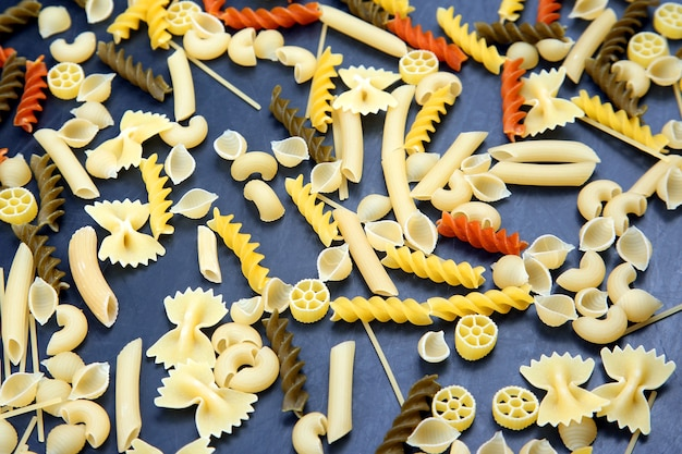 Différents types de pâtes italiennes colorées sur fond sombre. texture de la nourriture. produits à base de farine et aliments en cuisine