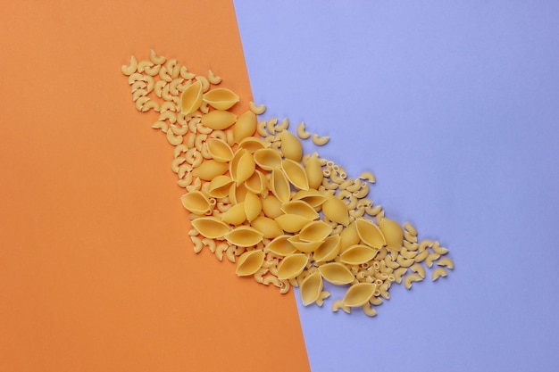 Différents types de pâtes italiennes crues sur fond violet marron.