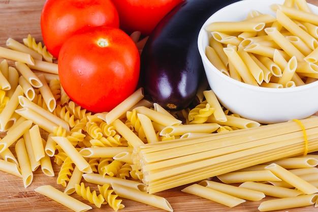 Différents types de pâtes italiennes crues avec tomates et autres légumes, vue de dessus. focus sélectionné.
