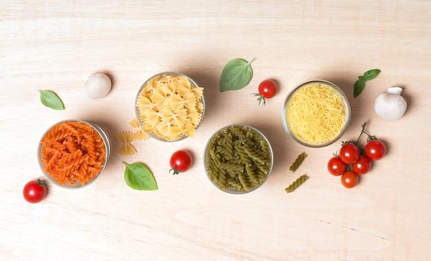 Différents types de pâtes italiennes avec des légumes sur la table
