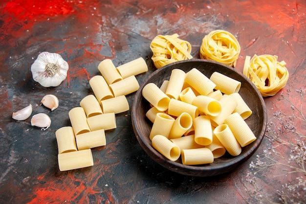 Différents types de pâtes non cuites à l'intérieur et à l'extérieur du pot brun et de l'ail sur le tableau noir