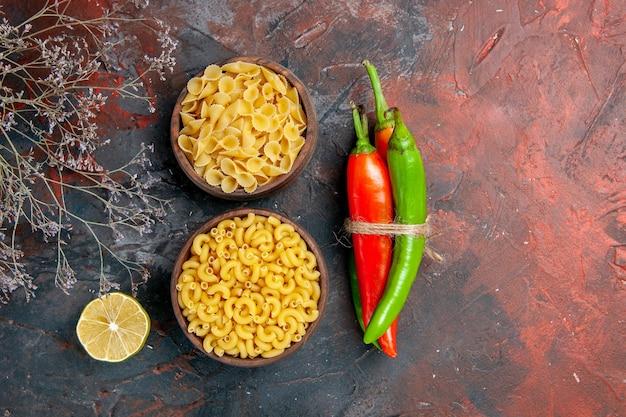 Différents types de pâtes non cuites poivrons de cayenne de différentes couleurs et tailles liées les unes aux autres avec une corde sur fond de couleur mixte