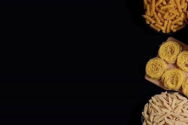 Différents types de pâtes sèches sur l'assiette et dans des bols sur walld noir. espace pour le texte, vue de dessus