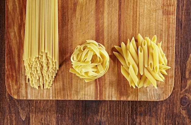 Différents types de pâtes sur table en bois avec planche à découper, vue de dessus. pappardelle, spaghetti, pâtes penne sur table en bois foncé.