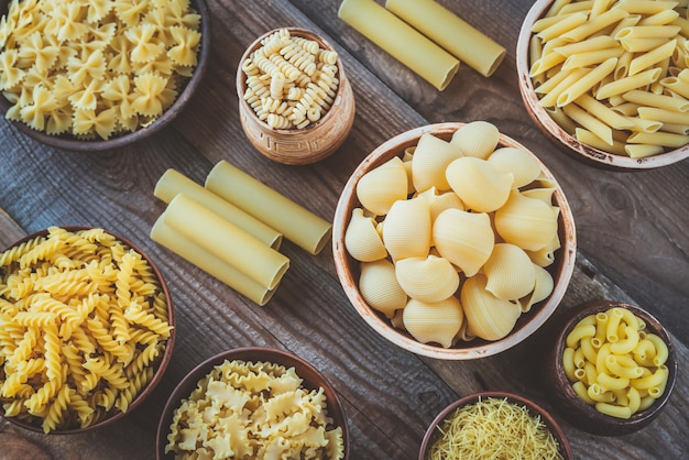 Différents types de pâtes sur table en bois