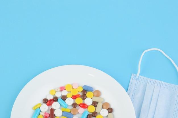 Différents types de pilules, gélules se trouvent sur une plaque blanche, à côté d'un masque médical bleu sur fond bleu. concept de soins de santé