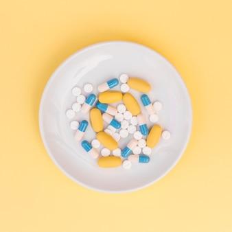 Différents types de pilules sur une plaque blanche sur fond jaune