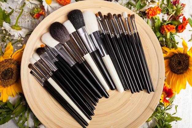 Différents types de pinceaux de maquillage sur une assiette à côté de fleurs sauvages sur fond de bois