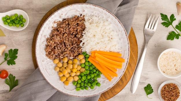 Différents types de porridge avec des légumes cuits sur une planche de bois