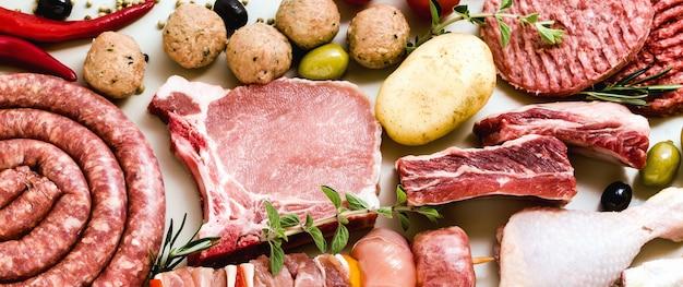 Différents types de rabanner de différents types de viande crue: cuisses de poulet, hamburgers de porc et de boeuf, côtes levées et brochettes, boulettes de viande de dinde, prêts à être cuits avec des pommes de terre,