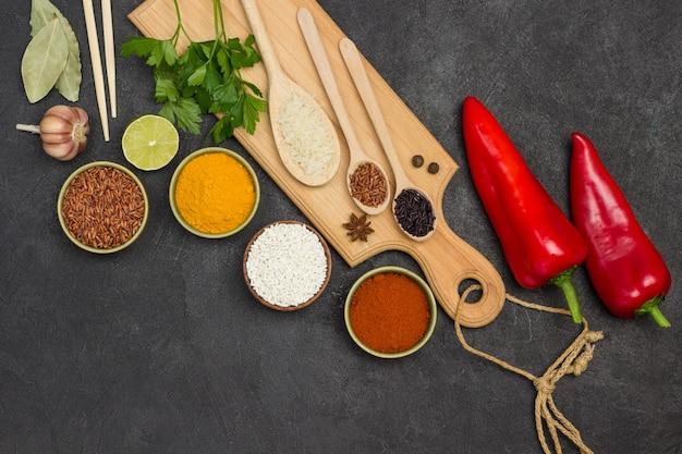Différents types de riz et d'épices sèches dans des bols. poivron rouge cru. bâtons de bambou. mise à plat.