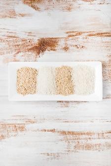 Différents types de riz non cuit dans un petit plateau blanc sur un fond rustique