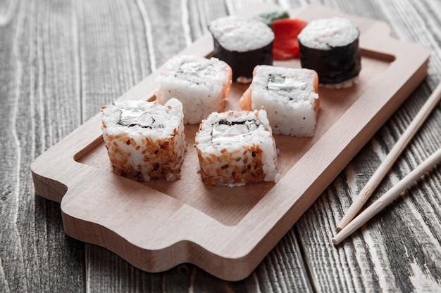 Différents types de rouleaux japonais avec du wasabi et du gingembre sur un plateau en bambou sur du bois