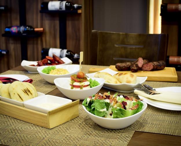 Différents types de salades avec du bois et des bouteilles de vin