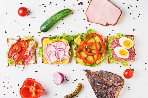 Différents types de sandwich et ingrédients sur fond blanc, vue de dessus