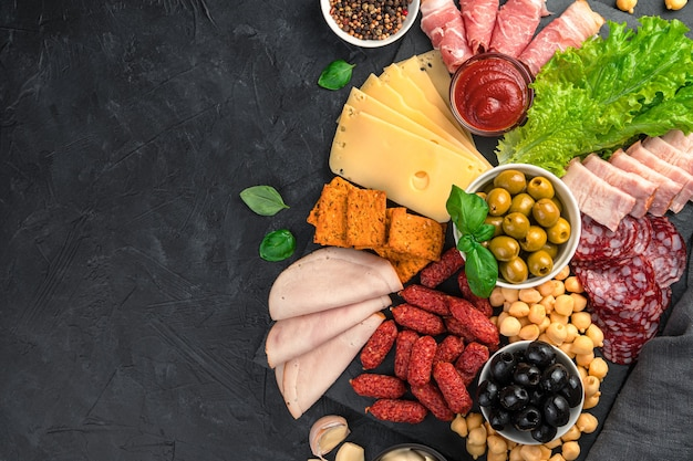 Différents types de saucisses et de fromage aux olives et salade sur un bureau noir. vue de dessus.
