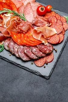 Différents types de saucisses et parmes salami bio séchées sur une surface en béton
