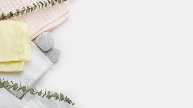 Différents types de serviettes pliées avec des pierres de spa et des brindilles sur fond blanc