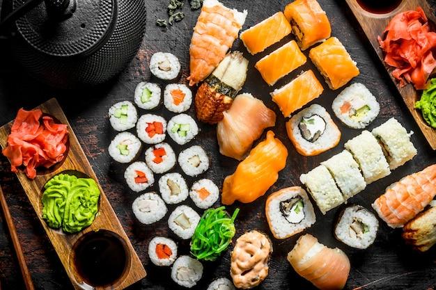 Différents types de sushis japonais, rouleaux et makis avec sauce, wasabi et thé vert dans une théière.