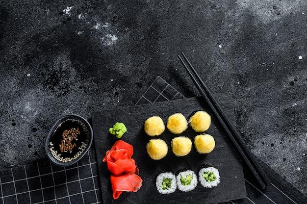 Différents types de sushis servis sur pierre noire. vue de dessus.