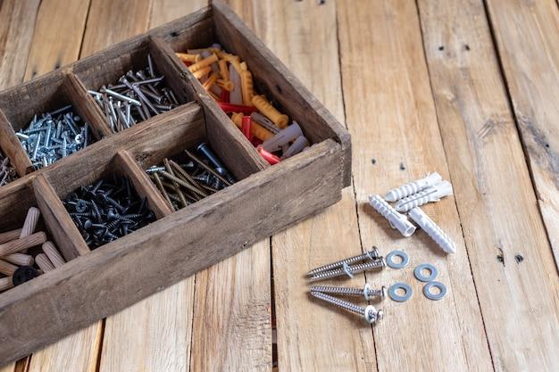 Différents types et tailles de vis dans une boîte de rangement en bois
