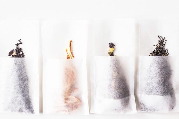 Différents types de thé en paquets de filtres jetables alignés dans un rang sur un fond blanc. vue de dessus, plat poser