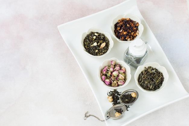 Différents types de thé sur un plateau blanc et une théière