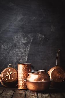Différents types d'ustensiles de cuisine en cuivre vintage sur sombre
