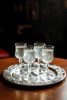 Différents types de vermouth blanc dans de petits verres à liqueur sur un plateau d'argent