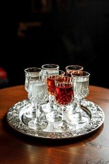 Différents types de vermouth dans de petits verres à liqueur sur un plateau d'argent