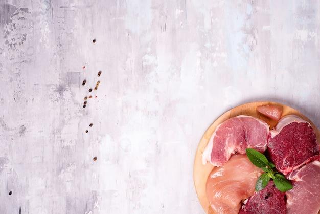 Différents types de viande sur une planche de bois. protéines maigres.