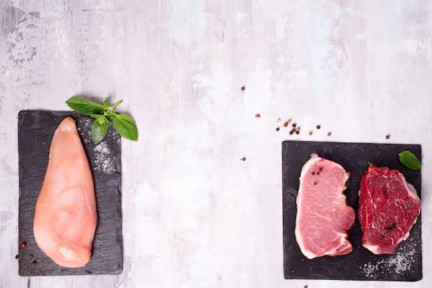 Différents types de viande sur une planche à découper en ardoise foncée. protéines maigres.