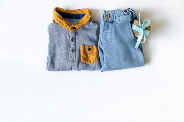 Différents vêtements pour enfants, accessoires avec boîte-cadeau sur table blanche avec espace de copie, mise à plat. douche de bébé, décorations, trucs, cadeau pour l'anniversaire d'un garçon, fête du nouveau-né.