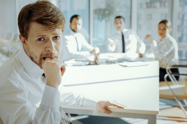 En difficulté. agité jeune manager assis à la réunion avec le conseil d'administration et se mordant le doigt, étant stressé