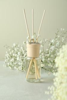Diffuseur et fleurs sur table texturée blanche