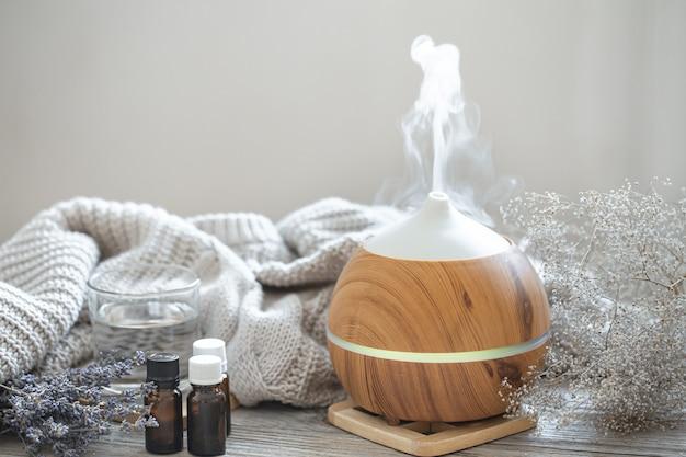 Diffuseur d'huile d'arôme moderne sur surface en bois avec élément tricoté, eau et huiles dans des pots.