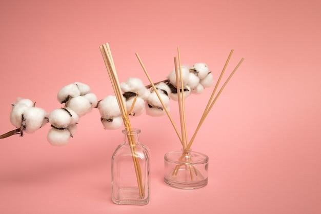 Diffuseurs à roseaux sur fond rose. désodorisants avec des boules de fleurs de coton odeur douce pour la maison. bâtonnets aromatiques à l'odeur florale. mise à plat commerciale, maquette vue de face. parfum d'aromathérapie