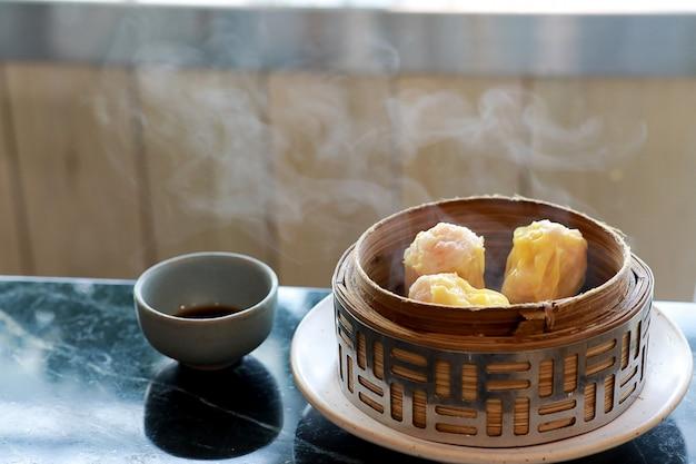 Dim sum de crevettes à la vapeur dans un paquebot en bambou avec de la fumée et de la sauce dans les tasses
