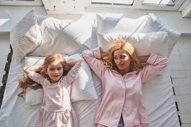 Dimanche matin. vue de dessus de la belle jeune mère et de sa fille mignonne gardant les mains derrière la tête et souriant en position couchée sur le lit à la maison