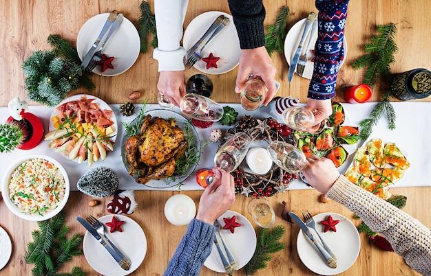 Dinde au four. dîner de noël. la table de noël est servie avec une dinde, décorée de guirlandes lumineuses et de bougies. poulet frit, table. dîner de famille. vue de dessus, mains dans le cadre