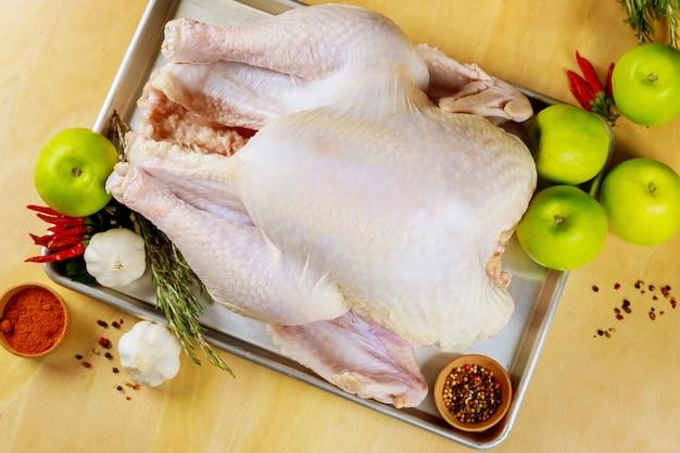 Dinde crue entière dans un plat allant au four prêt pour la cuisson. vue de dessus.