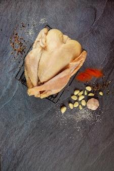 Dinde crue avec ingrédients de cuisine et épices sur une surface sombre.